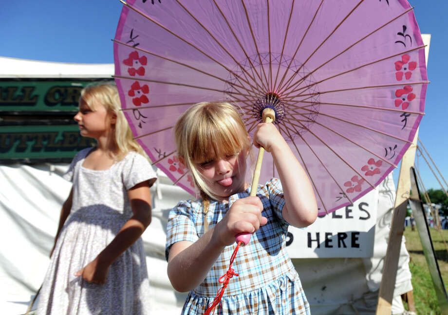 Mackenzie Iesenhower, 5, plays with her umbrella while she helps sell bottled water at the Blue Gray Alliance event in Gettysburg, Pa. on Saturday, June 29, 2013. Photo: Jason Plotkin, Associated Press / York Daily Record/Sunday News
