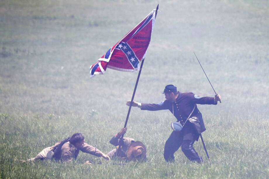 William H. Hincks, right, portrays his great, great, grandfather Medal of Honor recipient William Bliss Hincks taking a Confederate flag from a color bearer portrayed by Skip Koontz, center, of Sharpsburg Md., at a re-enactment of Pickett's Charge during ongoing activities commemorating the 150th anniversary of the Battle of Gettysburg, Sunday, June 30, 2013, at Bushey Farm in Gettysburg, Pa. Photo: Matt Rourke, Associated Press / AP