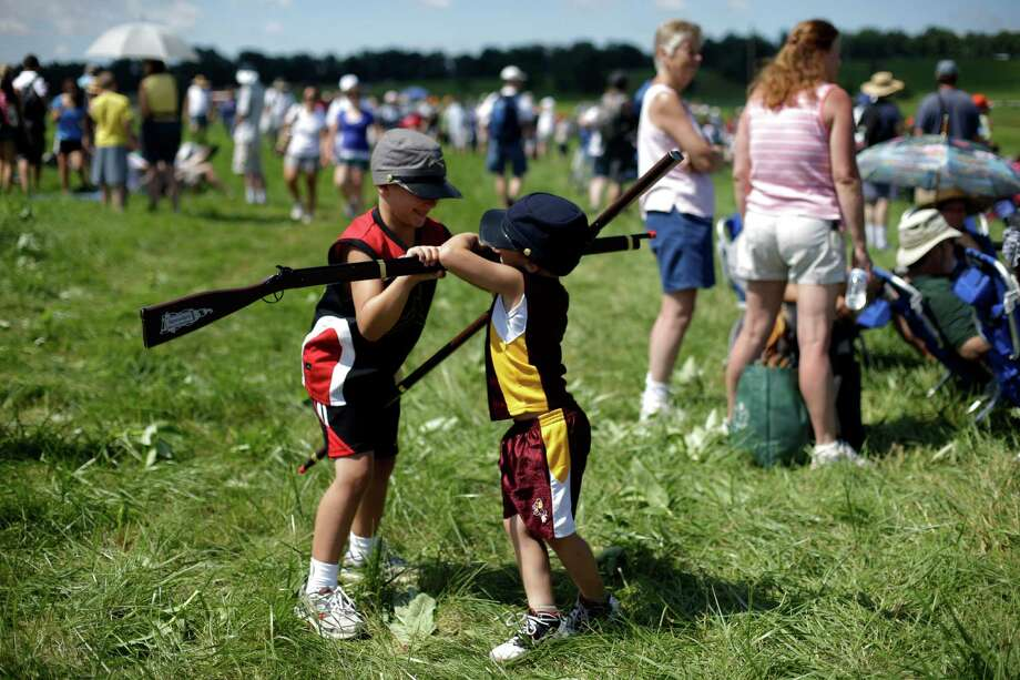 In this Saturday, June 29, 2013 photo, Luke Johnson, 6, left, and his brother Andrew Johnson, 5, of Carterville, Ill., play after a re-enactment during ongoing activities commemorating the 150th anniversary of the Battle of Gettysburg, at  Bushey Farm in Gettysburg, Pa. Photo: Matt Rourke, Associated Press / AP