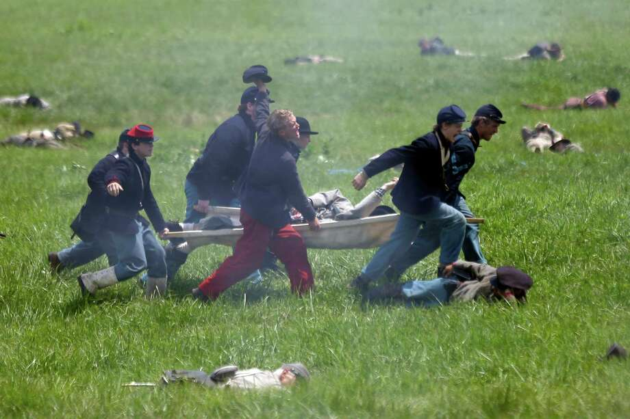In this June 30, 2013 file photo, re-enactors carry a person on a stretcher as they perform Pickett's Charge during ongoing activities commemorating the 150th anniversary of the Battle of Gettysburg at Bushey Farm in Gettysburg, Pa. Photo: Matt Rourke, Associated Press / AP