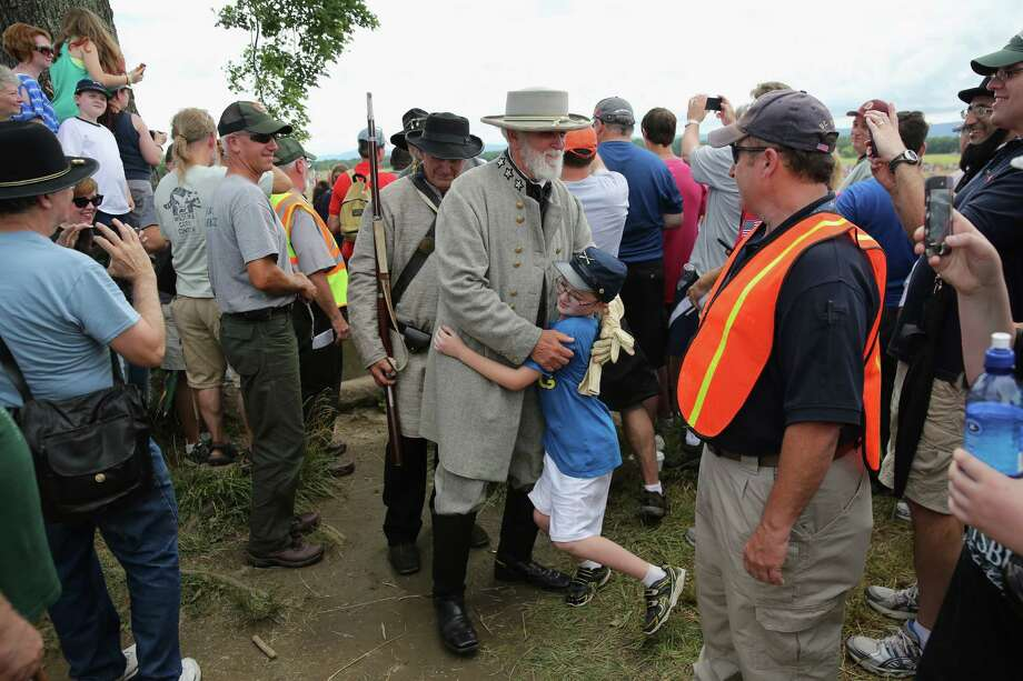 A boy hugs a General Lee re-enactor after thousands of people re-enacted Pickett's Charge on the 150th anniversary of the historic Battle of Gettysburg on July 3, 2013 in Gettysburg, Pennsylvania . The Rebel charge, which occurred on July 3, 1863, the last day of the three-day battle, was a decisive Union victory and widely considered the turning point in the American Civil War. Federal and Confederate armies suffered a combined total of 51,000 casualties over three days, the highest number of any battle in the four-year war. Photo: John Moore, Getty Images / 2013 Getty Images