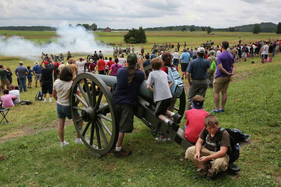 Tourists watch Confederate Civil War re-enactors fire a cannon on the 150th anniversary of the historic Battle of Gettysburg on July 2, 2013 in Gettysburg, Pennsylvania. The battle, which took place July 1-3, 1863, is widely considered the turning point in the American Civil War in favor of the Union. Federal and Confederate armies suffered a combined total of 51,000 casualties over three days, the highest number of any battle in the four-year war. Photo: John Moore, Getty Images / 2013 Getty Images