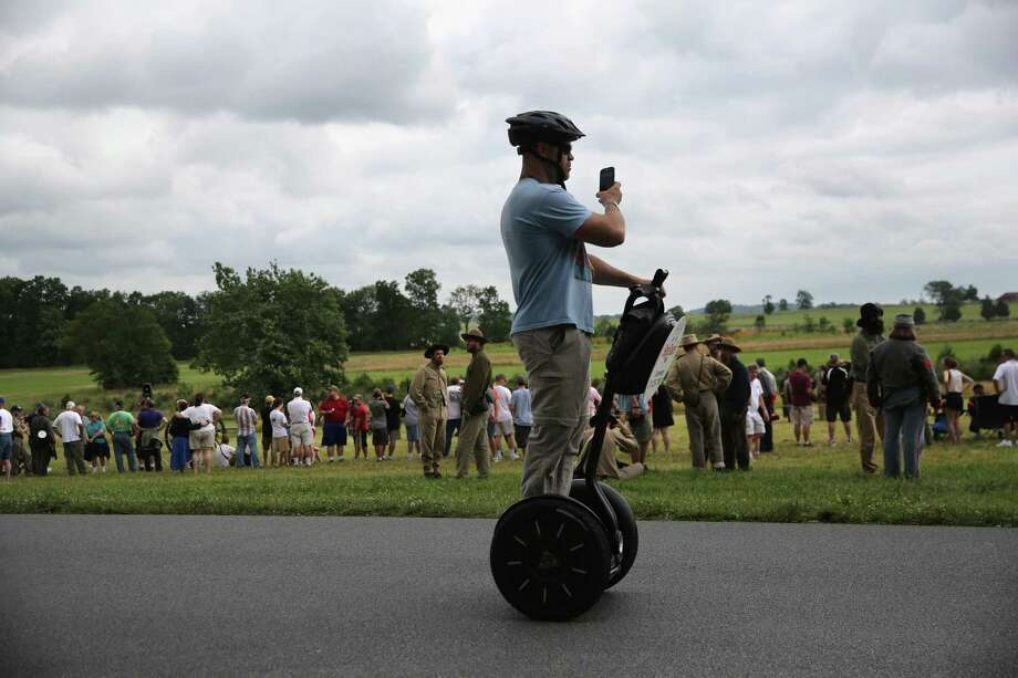 Tourist on a Segway watches as Confederate Civil War re-enactors stage a demonstration on the 150th anniversary of the historic Battle of Gettysburg on July 2, 2013 in Gettysburg, Pennsylvania. The battle, which took place July 1-3, 1863, is widely considered the turning point in the American Civil War in favor of the Union. Federal and Confederate armies suffered a combined total of 51,000 casualties over three days, the highest number of any battle in the four-year war. Photo: John Moore, Getty Images / 2013 Getty Images