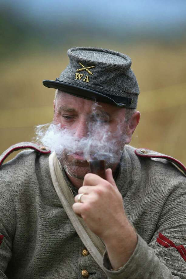 A Confederate Civil War re-enactor smokes a pipe before an artillery re-enactment on the 150th anniversary of the historic Battle of Gettysburg on July 2, 2013 in Gettysburg, Pennsylvania. The battle, which took place July 1-3, 1863, is widely considered the turning point in the American Civil War in favor of the Union. Federal and Confederate armies suffered a combined total of 51,000 casualties over three days, the highest number of any battle in the four-year war. Photo: John Moore, Getty Images / 2013 Getty Images