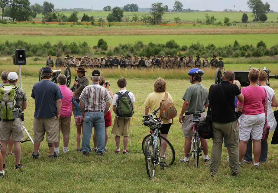 Tourists watch Confederate Civil War re-enactors on the 150th anniversary of the historic Battle of Gettysburg on July 2, 2013 in Gettysburg, Pennsylvania. The battle, which took place July 1-3, 1863, is widely considered the turning point in the American Civil War in favor of the Union. Federal and Confederate armies suffered a combined total of 51,000 casualties over three days, the highest number of any battle in the four-year war. Photo: John Moore, Getty Images / 2013 Getty Images
