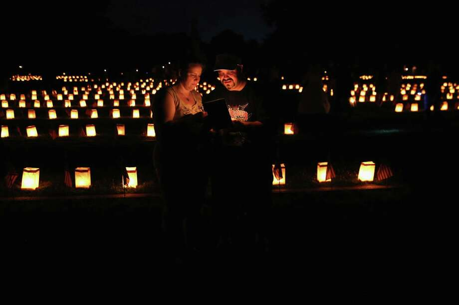 Frank Marron and Colleen Miller stand amidst luminaries marking Civil War graves at the Soldiers' National Cemetery on June 30, 2013 in Gettysburg, Pennsylvania. Hundreds of people gathered for the official Civil War ceremony marking the 150th anniversary of the Battle of Gettysburg. The battle is widely considered the turning point in the Civil War and a watershed moment in U.S. history. Union and Confederate armies suffered a combined total of up to 51,000 casualties over three days, the highest number of any battle in the four-year war. Photo: John Moore, Getty Images / 2013 Getty Images