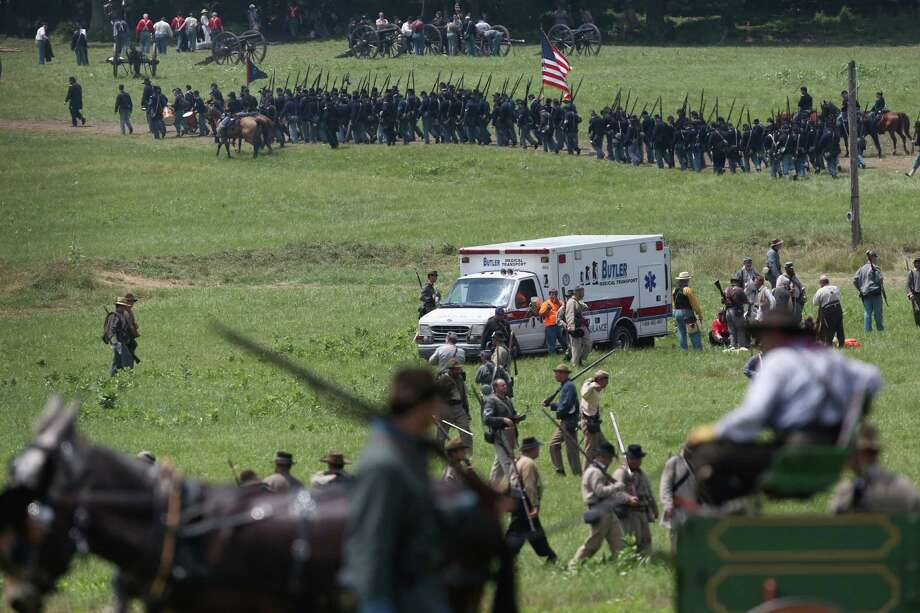 An ambulance departs at the end of Pickett's Charge on the last day of a Battle of Gettysburg re-enactment on June 30, 2013 in Gettysburg, Pennsylvania. Several people were taken away from the event due to heat exhaustion. Some 8,000 re-enactors from the Blue Gray Alliance participated in the re-enactment, marking the 150th anniversary of the July 1-3, 1863 Battle of Gettysburg. Confederate General Robert E. Lee's Army of Northern Virginia was routed during the doomed frontal assault, considered the turning point in the Civil War and a watershed moment in U.S. history. Union and Confederate armies suffered a combined total of up to 51,000 casualties over three days, the highest number of any battle in the four-year war. Pickett's charge was named for the Confederate Maj. General George Pickett, whose division of rebel troops was annhilated in the attack. Photo: John Moore, Getty Images / 2013 Getty Images