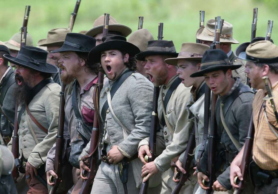 Confederate Civil War re-enactors march towards Union lines during Pickett's Charge on the last day of a Battle of Gettysburg re-enactment on June 30, 2013 in Gettysburg, Pennsylvania. Some 8,000 re-enactors from the Blue Gray Alliance participated in the event, marking the 150th anniversary of the July 1-3, 1863 Battle of Gettysburg. Confederate General Robert E. Lee's Army of Northern Virginia was routed during the doomed frontal assault, considered the turning point in the Civil War and a watershed moment in U.S. history. Union and Confederate armies suffered a combined total of up to 51,000 casualties over three days, the highest number of any battle in the four-year war. Pickett's charge was named for the Confederate Maj. General George Pickett, whose division of rebel troops was annhilated in the attack. Photo: John Moore, Getty Images / 2013 Getty Images