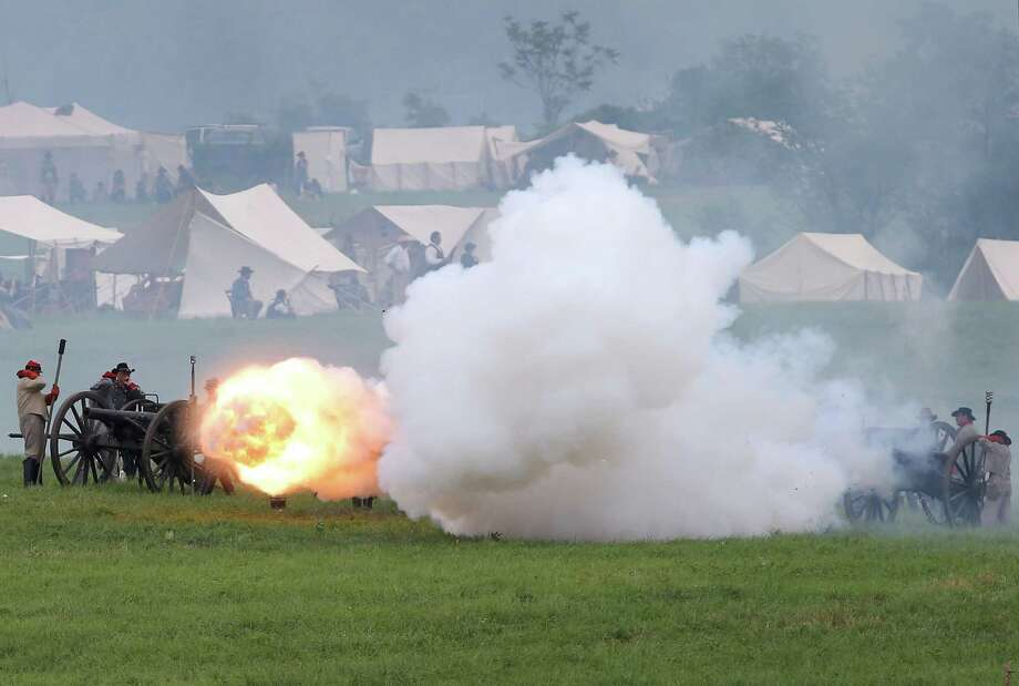Confederate Civil War re-enactors fire cannon towards Union positions ahead  of Pickett's Charge on the last day of a Battle of Gettysburg re-enactment on June 30, 2013 in Gettysburg, Pennsylvania. Some 8,000 re-enactors from the Blue Gray Alliance participated in the event, marking the 150th anniversary of the July 1-3, 1863 Battle of Gettysburg. Confederate General Robert E. Lee's Army of Northern Virginia was routed during the doomed frontal assault, considered the turning point in the Civil War and a watershed moment in U.S. history. Union and Confederate armies suffered a combined total of up to 51,000 casualties over three days, the highest number of any battle in the four-year war. Pickett's charge was named for the Confederate Maj. General George Pickett, whose division of rebel troops was annhilated in the attack. Photo: John Moore, Getty Images / 2013 Getty Images