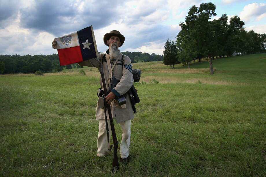 Civil War re-enactor Randy Whitaker from Hood's Texas Brigade displays the Texas flag during a three-day Battle of Gettysburg re-enactment on June 29, 2013 in Gettysburg, Pennsylvania. Some 8,000 re-enactors from around the United States are participating in events marking the 150th anniversary of the July 1-3, 1863 Battle of Gettysburg. General Robert E. Lee's Army of Northern Virginia was defeated on the third day of the battle, considered the turning point in the American Civil War and a watershed moment in the nation's history. Union and Confederate armies suffered a combined total of some 46,000-51,000 casualties over three days, the highest of any battle the four-year war. Photo: John Moore, Getty Images / 2013 Getty Images