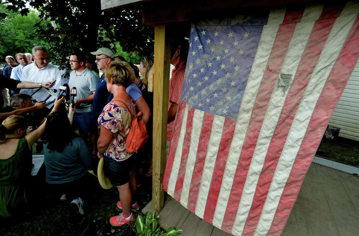 With Senator Charles Schumer, left, listening, Michael Sheeley, second from left, speaks about his grandmother Ethel Healey during a press conference Wednesday July 3, 2013, in Fort Plain, N.Y. The American flag, which was loved by Ethel Healey, survived the flooding and was hung on the remaining building on Healey's property. (Skip Dickstein/Times Union)