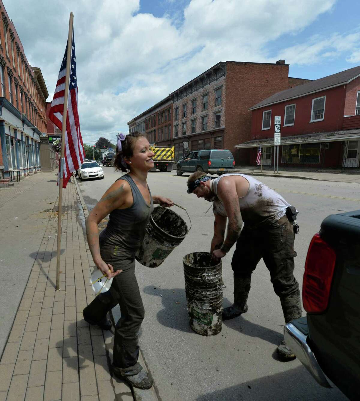 Volunteers Laura Harrison of Amsterdam and Jake Kruger from Tribes Hill put their buckets in their truck before going home for the day Wednesday July 3, 2013, after assisting in the clean up of 52 Main Street in Fort Plain, N.Y. (Skip Dickstein/Times Union)