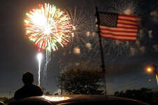 A spectator watches the fireworks display at Short Beach in Stratford, Conn. on Wednesday July 3, 2013.