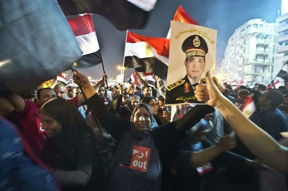 People celebrate at Tahrir Square with a portrait of army chief Abdel-Fattah Sissi after a broadcast confirming that the army will temporarily be taking over the country. Photo: Khaled Desouki / AFP / Getty Images