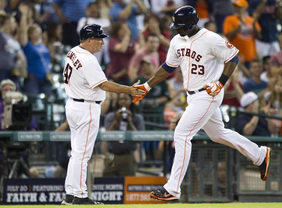 Astros left fielder Chris Carter slaps hands with third base coach Dave Trembley as he rounds third after a solo home in the second inning.