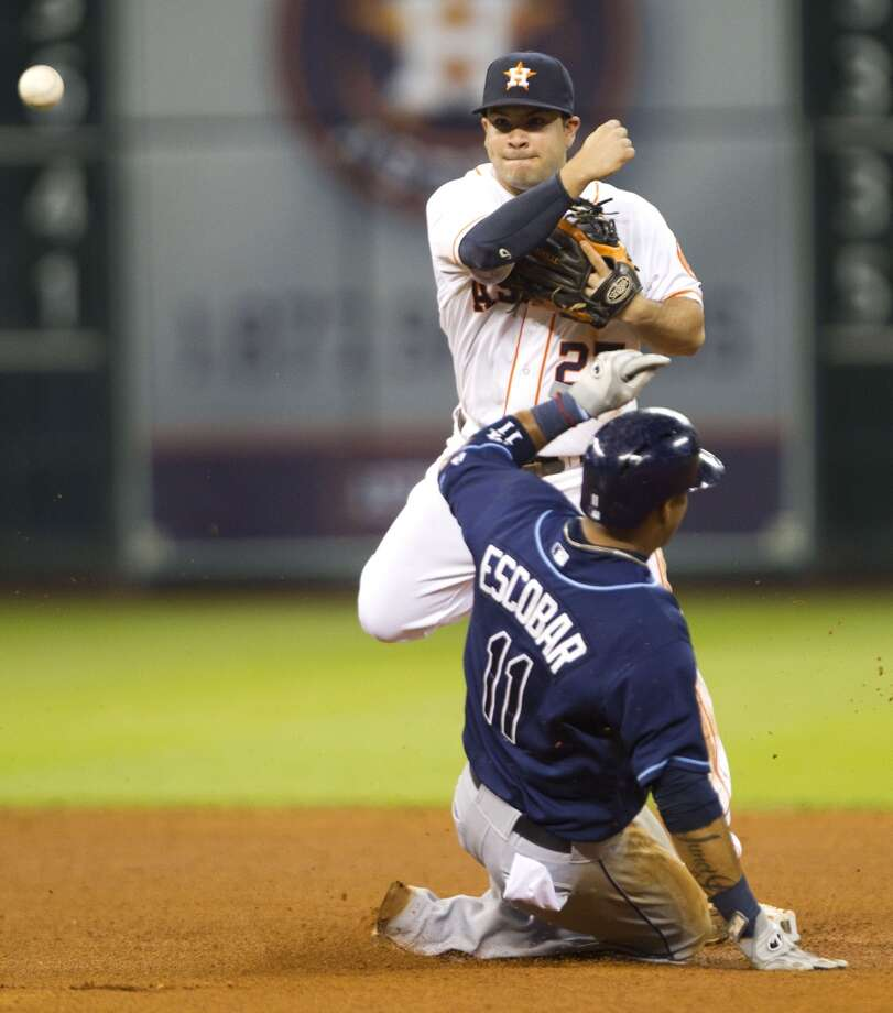Astros second baseman Jose Altuve turns a double play over Rays shortstop Yunel Escobar.