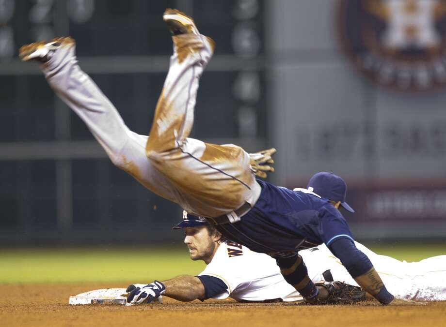 Astros first baseman Brett Wallace slides safely under Rays shortstop Yunel Escobar on a double to left.