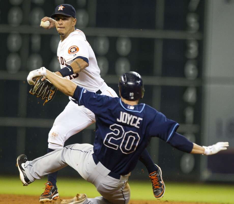 Astros shortstop Ronny Cedeno turns a double play over Rays right fielder Matt Joyce.