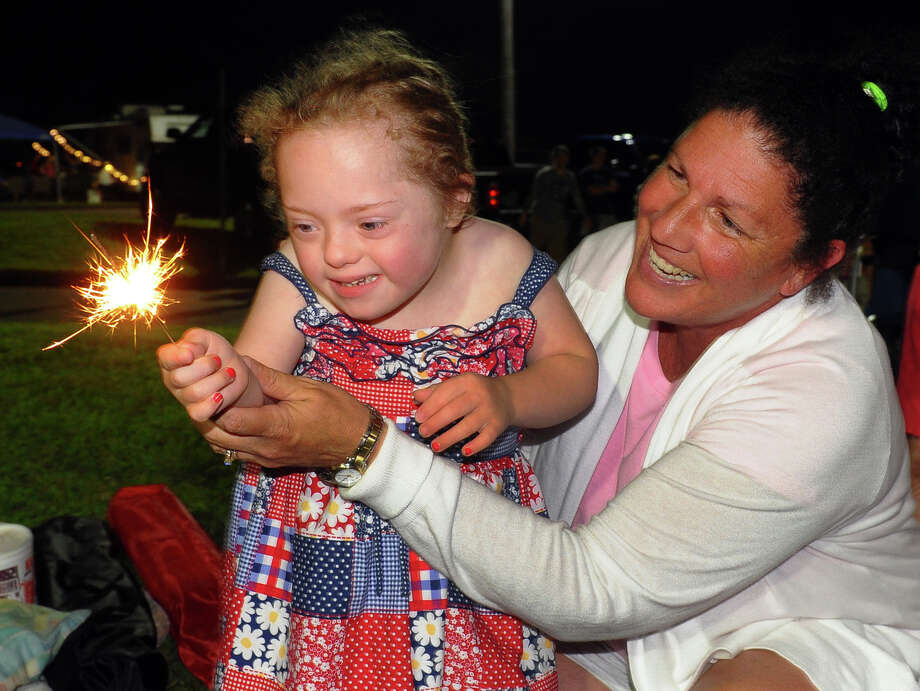 Mary Kathryn Llewelyn, 5, plays with a sparkler as her mom Kate helps her hold it, during the July 4th celebration held at Short Beach in Stratford, Conn. on Wednesday July 3, 2013. Photo: Christian Abraham / Connecticut Post