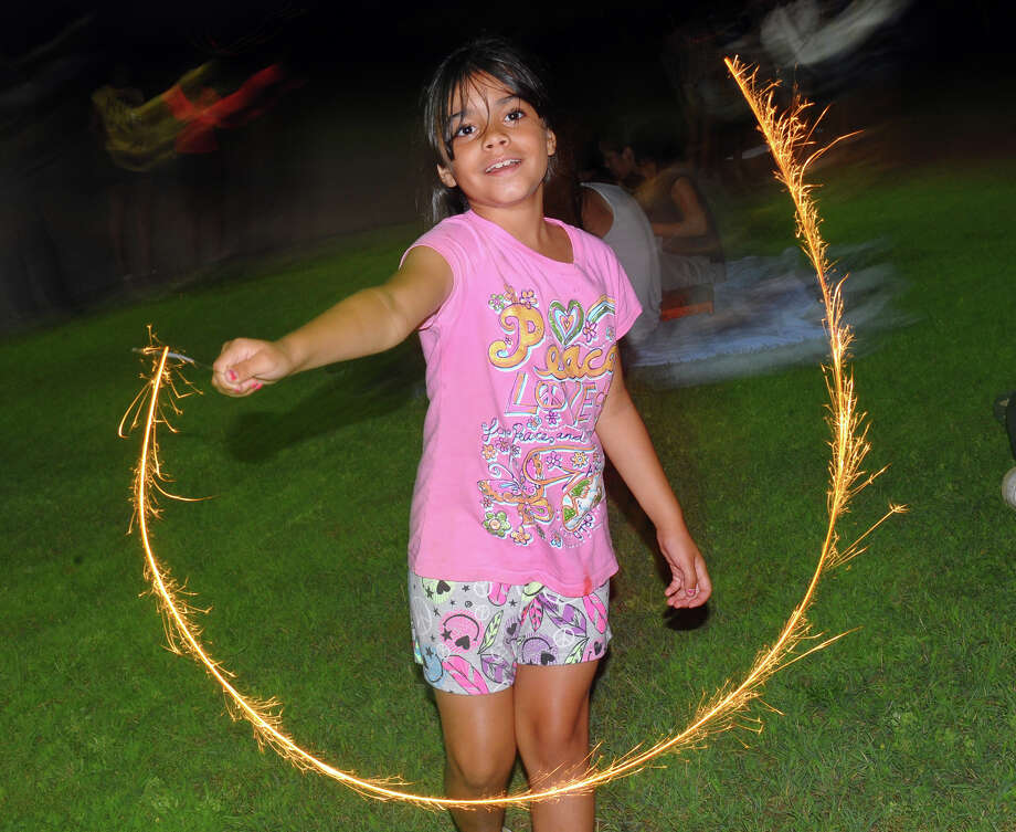 Angela Marter, 8, plays with a sparkler during the July 4th celebration held at Short Beach in Stratford, Conn. on Wednesday July 3, 2013. Photo: Christian Abraham / Connecticut Post