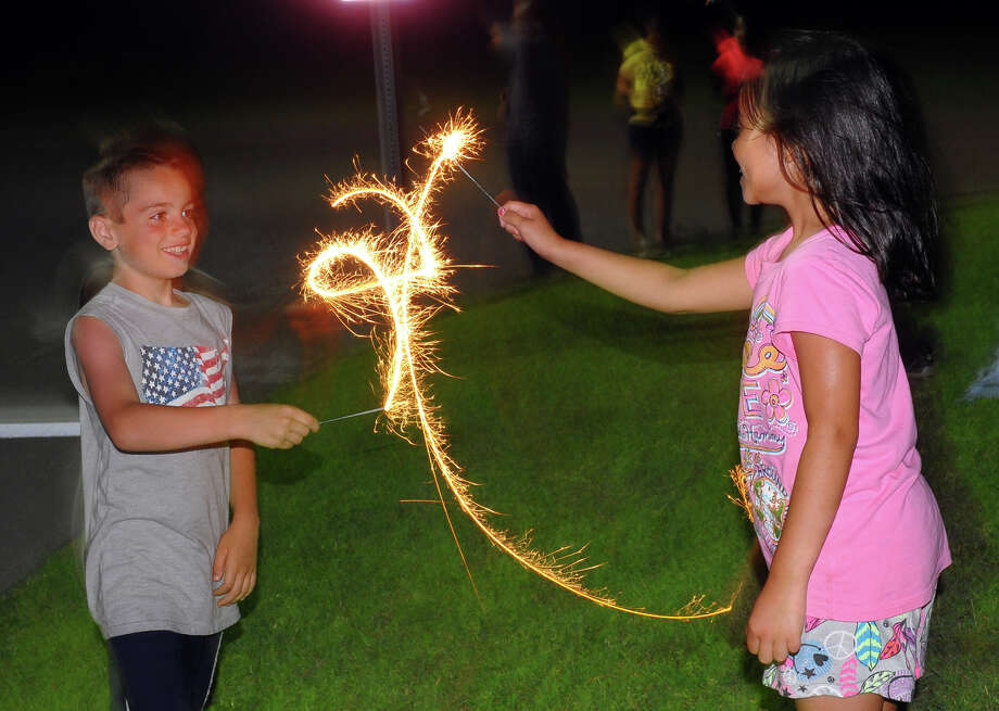 Lenny Ialeggio, 8, and his cousin Angela Marter, 8, play with a sparklers during the July 4th celebration held at Short Beach in Stratford, Conn. on Wednesday July 3, 2013. Photo: Christian Abraham / Connecticut Post