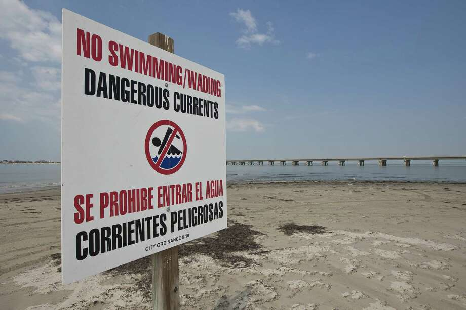 Caution signs stand along the beach at San Luis Pass, where four people have drowned recently. Photo: Nick De La Torre / Houston Chronicle