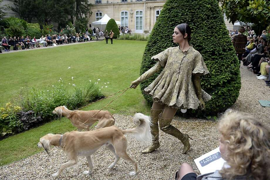 A model walks with dogs as she presents a creation by Frank Sorbier during the Haute Couture Fall-Winter 2013/2014 collection show, on July 3, 2013 in Paris.  AFP PHOTO/MARTIN BUREAUMARTIN BUREAU/AFP/Getty Images Photo: Martin Bureau, AFP/Getty Images