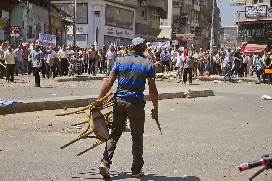 An Egyptian opposition protester holds a chair and knife during a clash between supporters and opponents of President Mohammed Morsi in downtown Damietta, Egypt, Wednesday, July 3, 2013. The deadline on the military's ultimatum to President Mohammed Morsi has expired, with 48 hours passing since the time it was issued. Giant cheering crowds of Morsi's opponents have been gathered in Cairo's Tahrir Square and other locations nationwide, waving flags furiously in expectation that the military will act to remove the Islamist president after the deadline ends.(AP Photo/Hamada Elrasam) Photo: Hamada Elrasam, Associated Press