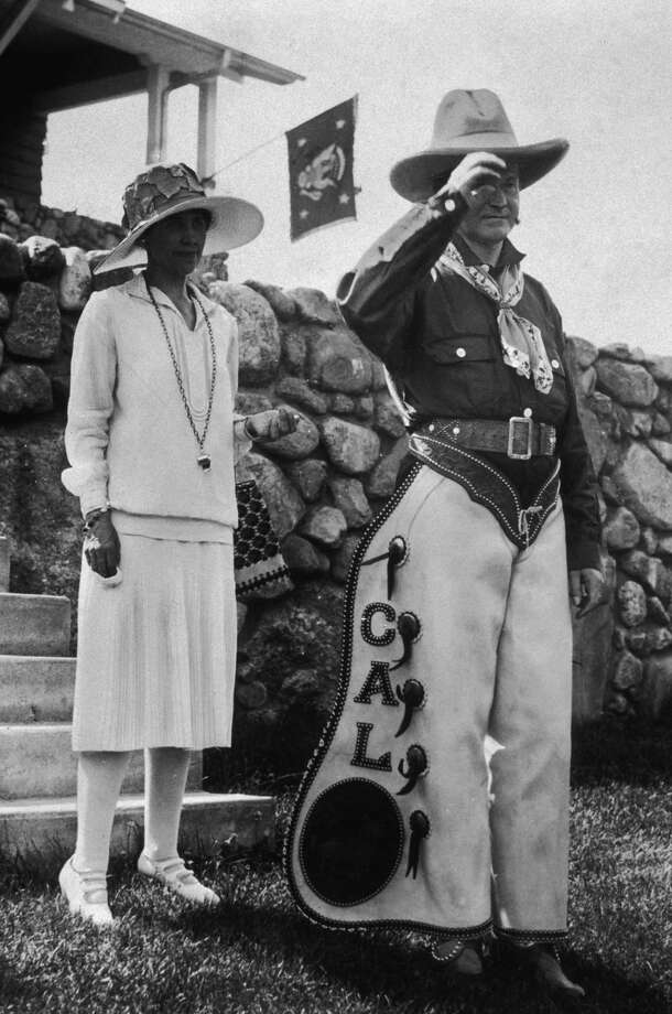4th June 1927:  American president Calvin Coolidge (1872 - 1933) and his wife, First Lady Grace Coolidge (1879 - 1957), pose outdoors at a party celebrating the 4th of July and his 55th birthday at the Summer White House, State Game Lodge and Resort, Custer State Park, South Dakota. Coolidge is wearing a cowboy outfit, which includes a pair of personalized chaps. Photo: New York Times Co., Getty Images / Archive Photos
