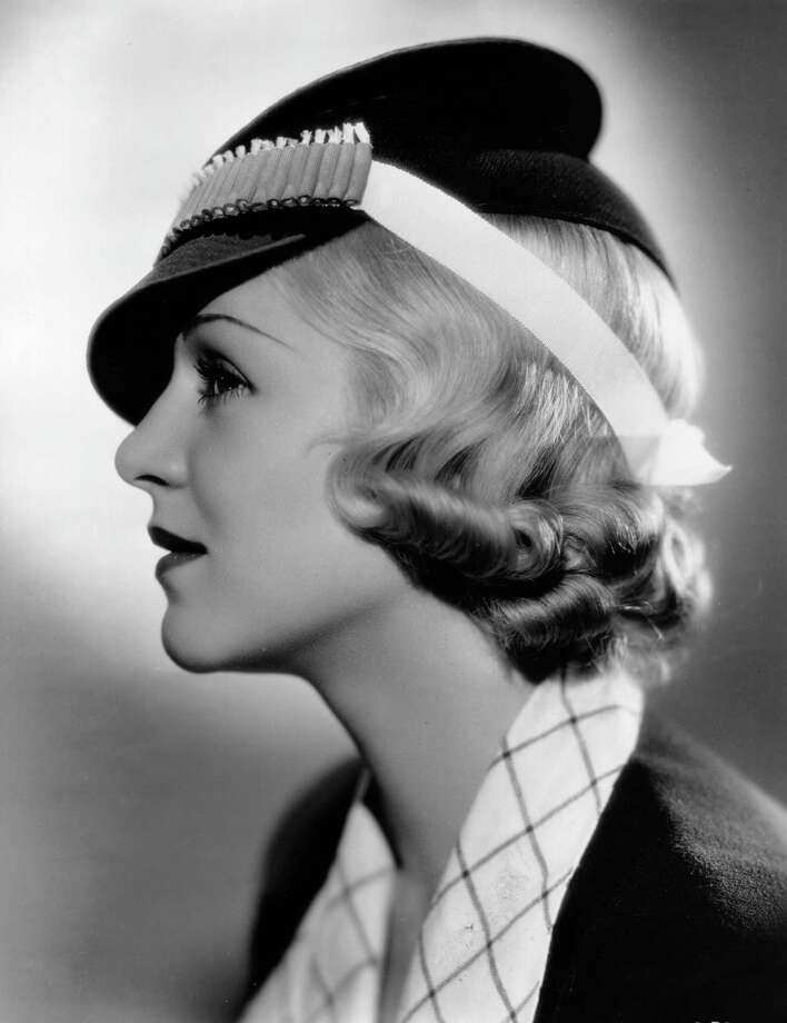 1936:  Claire Trevor (1909 - 2000) the stage name of Claire Wemlinger, the American character actress who made several routine movies before gaining recognition. She is modelling a firecracker hat, designed for Independence Day wear by Royer, the Fox Film stylist. Made of navy blue crepe, it is banded with red firecrackers ready for lighting. Photo: Hulton Archive, Getty Images / Hulton Archive
