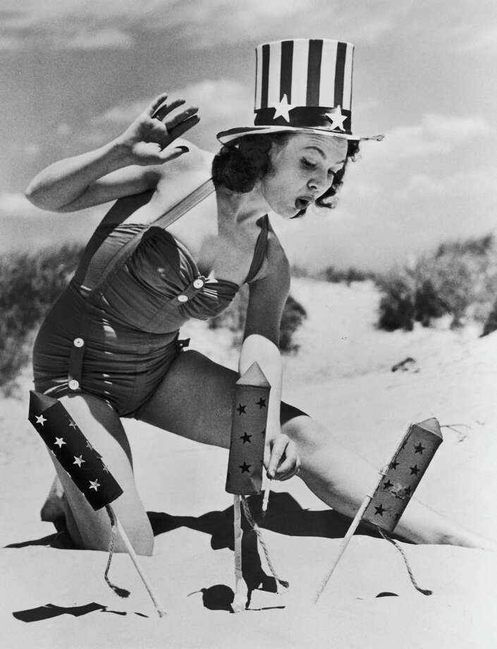 Actress Louise Synder wearing a patriotic hat to light fireworks on the beach during Fourth of July celebrations, circa 1950. Photo: FPG/Hulton Archive, Getty Images / 2008 Getty Images