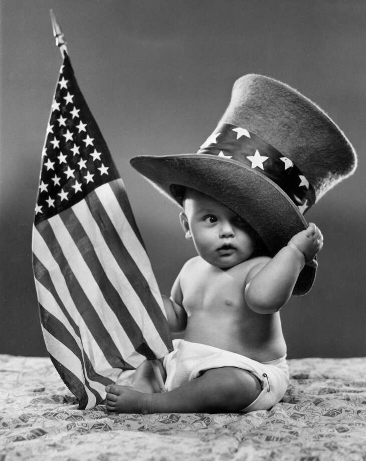 circa 1945:  A baby sits on a blanket, wearing an oversize top hat with a band of stars and holding an American flag. Photo: Lambert, Getty Images / Archive Photos
