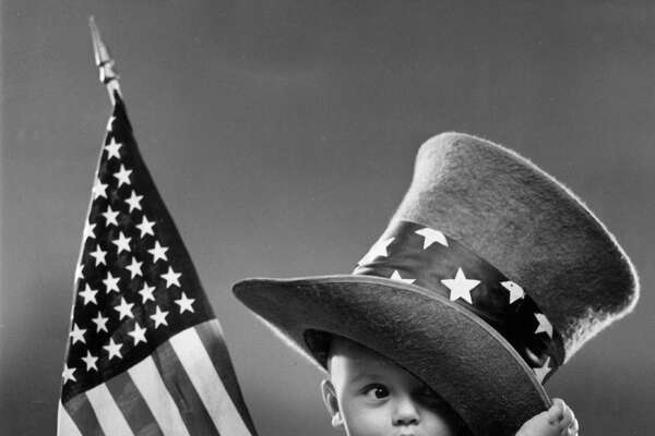 circa 1945: A baby sits on a blanket, wearing an oversize top hat with a band of stars and holding an American flag.