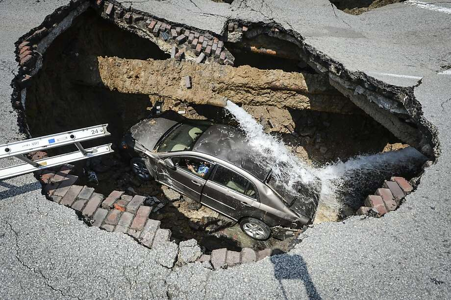 This photo provided by the Toledo, Ohio Fire and Rescue Department shows a car at the bottom of a sinkhole caused by a broken water line in Toledo, Ohio on Wednesday, July 3, 2013. Police say the driver, 60-year-old Pamela Knox of Toledo, was shaken up and didn't appear hurt but was taken to a hospital as a precaution. (AP Photo/Toledo, Ohio Fire and Rescue Department, Lt. Matthew Hertzfeld) Photo: Lt. Matthew Hertzfeld, Associated Press