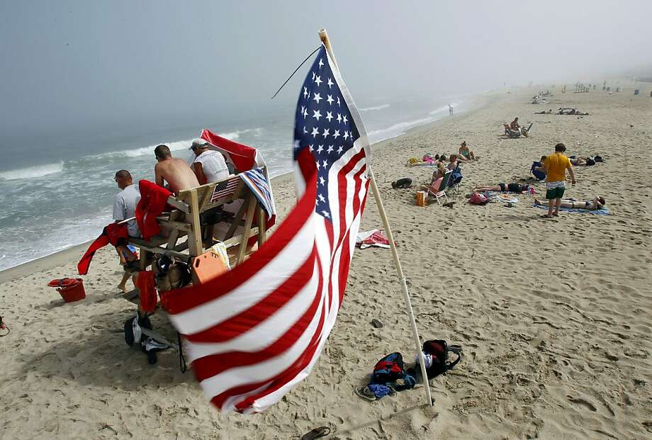 Lifeguards work as sunbathers lay out on a foggy beach Wednesday, July 3, 2013, in Belmar, N.J., ahead of the Fourth of July holiday. (AP Photo/Mel Evans) Photo: Mel Evans, Associated Press