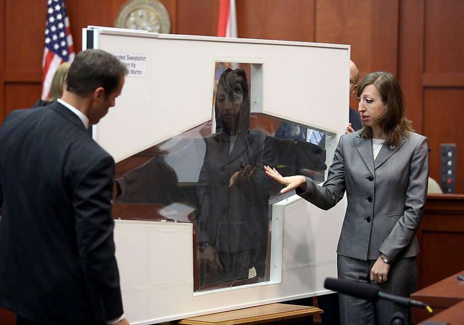 Amy Siewert, a firearms expert with the Florida Department of Law Enforcement, faces the jury as shows Trayvon Martin's hooded sweatshirt  in Seminole circuit court, in Sanford, Fla., Wednesday, July 3, 2013. Zimmerman is charged with second-degree murder in the fatal shooting of Trayvon Martin, an unarmed teen, in 2012. (AP Photo/Orlando Sentinel, Jacob Langston, Pool) Photo: Jacob Langston, Associated Press