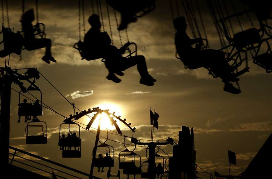 Carnival-goers ride into the sunsetat State Fair Meadowlands in East Rutherford, N.J. Photo: Julio Cortez, Associated Press