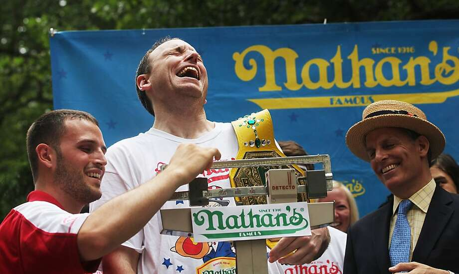 NEW YORK, NY - JULY 03:  Men's world record holder Joey Chestnut (C) laughs as he is weighed at the Nathan's Famous Fourth of July International Hot Dog Eating Contest weigh-in ceremony on July 3, 2013 in the Brooklyn borough of New York City. The annual hot dog eating event is expected to draw up to 40,000 fans on July 4, in the Coney Island section of Brooklyn.   (Photo by Mario Tama/Getty Images) *** BESTPIX *** Photo: Mario Tama, Getty Images