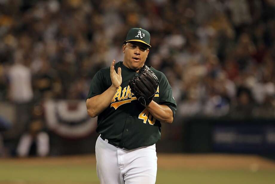 Bartolo Colon applauds a catch by Yoenis Cespedes as Colon works his way out of a jam in the seventh inning. The Oakland Athletics played the Chicago Cubs at O.co Coliseum in Oakland, Calif., on Wednesday, July 3, 2013. Photo: Carlos Avila Gonzalez, The Chronicle