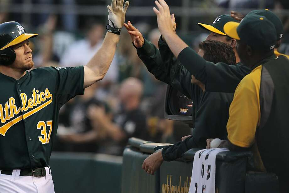 Brandon Moss celebrates his solo home run in the fourth inning with teammates in the dugout. The Oakland Athletics played the Chicago Cubs at O.co Coliseum in Oakland, Calif., on Wednesday, July 3, 2013. Photo: Carlos Avila Gonzalez, The Chronicle