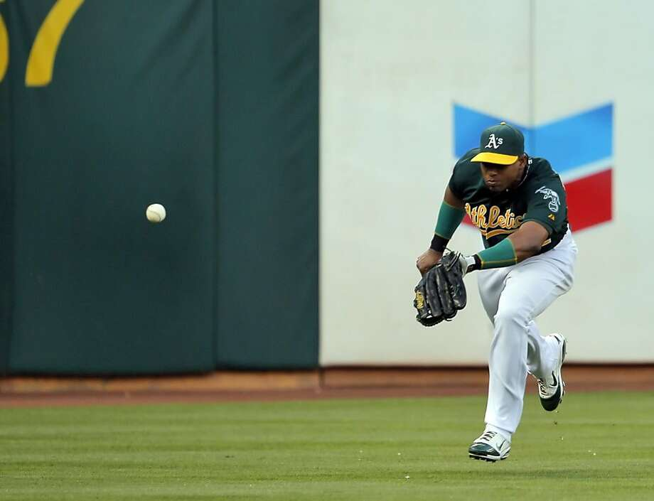 Yoenis Cespedes can't get his glove on a ball hit by Nate Schierholtz for a triple. The Oakland Athletics played the Chicago Cubs at O.co Coliseum in Oakland, Calif., on Wednesday, July 3, 2013. Photo: Carlos Avila Gonzalez, The Chronicle