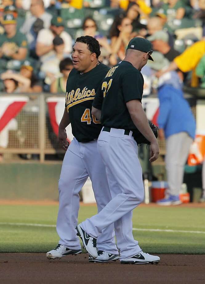Bartolo Colon smiles with Brandon Moss after sprinting to first to cover a ball hit to Moss in the first inning. The Oakland Athletics played the Chicago Cubs at O.co Coliseum in Oakland, Calif., on Wednesday, July 3, 2013. Photo: Carlos Avila Gonzalez, The Chronicle