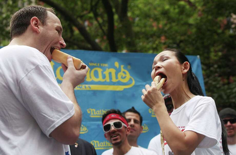NEW YORK, NY - JULY 03:  Men's world record holder Joey Chestnut (L) and women's world record holder Sonya Thomas eat a hot dog during the Nathan's Famous Fourth of July International Hot Dog Eating Contest weigh-in ceremony on July 3, 2013 in the Brooklyn borough New York City. The annual hot dog eating event is expected to draw up to 40,000 fans on July 4, in the Coney Island section of Brooklyn.  (Photo by Mario Tama/Getty Images) ORG XMIT: 173071810 Photo: Mario Tama, Getty / 2013 Getty Images