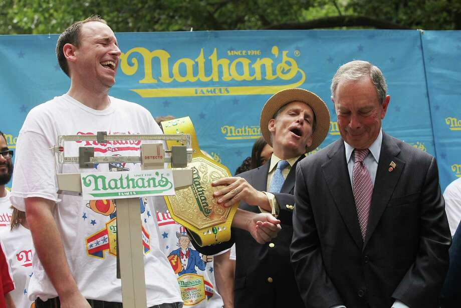 NEW YORK, NY - JULY 03:  Men's world record holder Joey Chestnut (L) is weighed as New York City Mayor Michael Bloomber (R) looks on during the Nathan's Famous Fourth of July International Hot Dog Eating Contest weigh-in ceremony on July 3, 2013 in the Brooklyn borough of New York City. The annual hot dog eating event is expected to draw up to 40,000 fans on July 4, in the Coney Island section of Brooklyn.  (Photo by Mario Tama/Getty Images) ORG XMIT: 173071810 Photo: Mario Tama, Getty / 2013 Getty Images