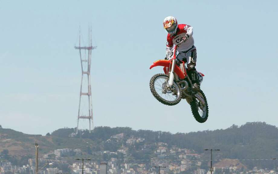 Supercross rider Brian Roth at the Pac Bell Park parking lot leaps in the air -- and into the photo with Sutro Tower. Photo: DEANNE FITZMAURICE, SFC / CHRONICLE