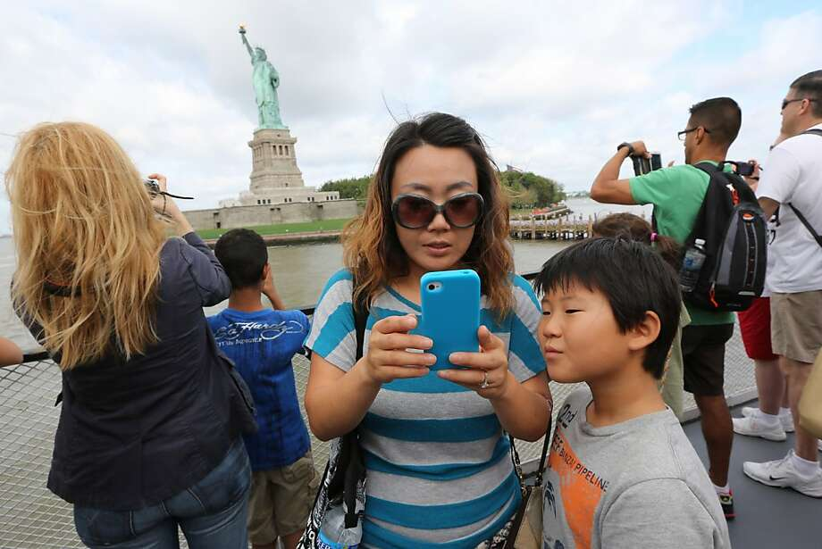 Visitors to fhe Statue of Liberty take photos as they arrive on the first tourist ferry to leave Manhattan, Thursday, July 4, 2013 at  in New York. The Statue of Liberty finally reopened on the Fourth of July months after Superstorm Sandy swamped its little island in New York Harbor as Americans across the country marked the holiday with fireworks and barbecues. Photo: Mary Altaffer, Associated Press