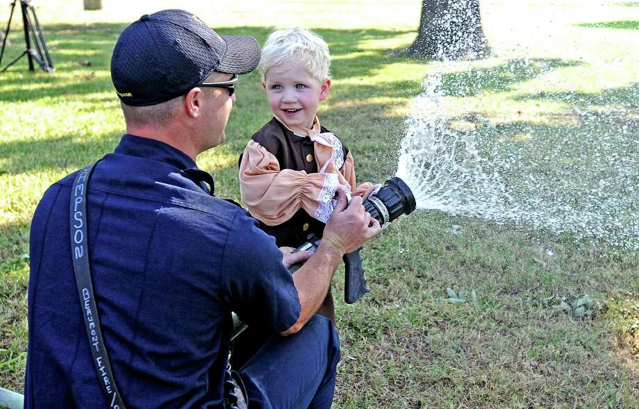 Three-year-old Conrad Morrison sprays the water hose with Beaumont Fire Fighter at the July 4th Parade on Thursday, July 4, 2013. Photo taken: Randy Edwards/The Enterprise