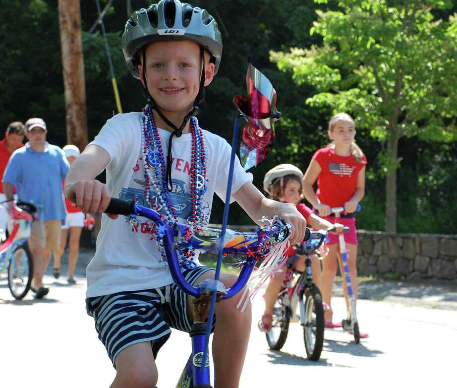 James Stratmann of Australia makes an annual visit to Connecticut with his family for his favorite holiday -- America's Independence Day -- and here rides in the annual July 4th bike parade through Southport. Photo: Jarret Liotta / Fairfield Citizen