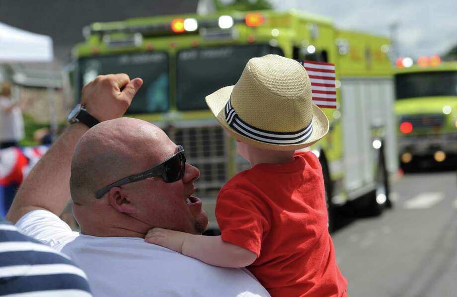 Lou Carollo, of New Fairfield, and his son, Danny Carollo, 2, cheer as the firetrucks pass by at the Annual Independence Day Parade in New Fairfield, Conn. on Thursday, July 4, 2013.  Hundreds of people lined the streets of downtown New Fairfield to watch the festivities, sponsored by the New Fairfield Lions Club. Photo: Tyler Sizemore / The News-Times