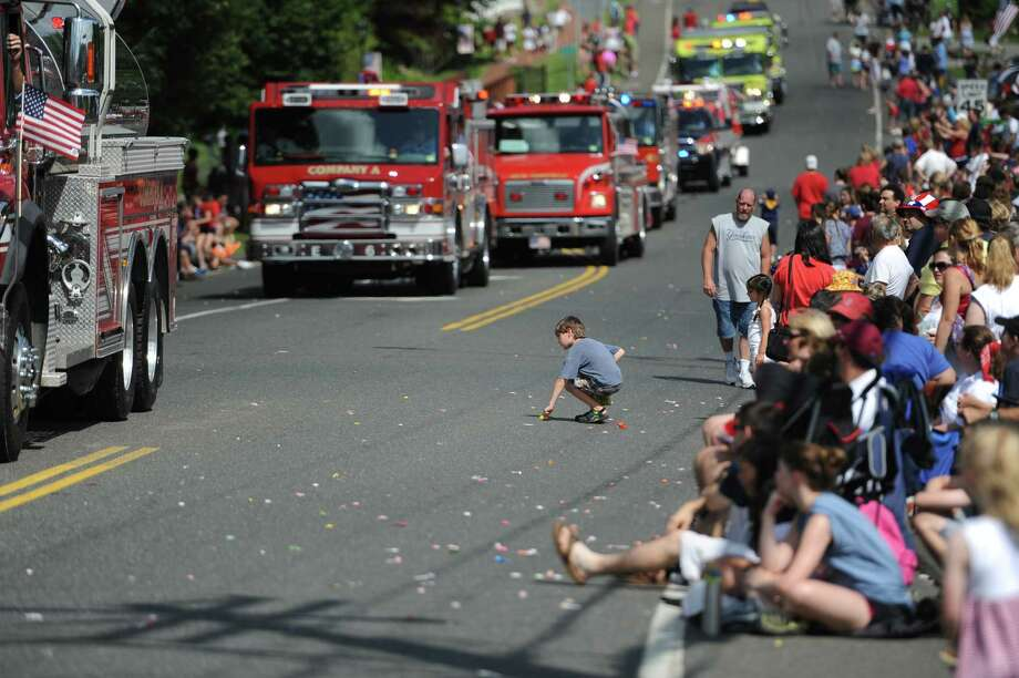 A child scrambles to pick up candy at the Annual Independence Day Parade in New Fairfield, Conn. on Thursday, July 4, 2013.  Hundreds of people lined the streets of downtown New Fairfield to watch the festivities, sponsored by the New Fairfield Lions Club. Photo: Tyler Sizemore / The News-Times